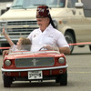 """Jimmy Downs, s driver for the Sharon Temple Shriners' """"Mustang Patrol,"""" smiles as his passenger Courtney Upton, 4, waves to her dad during the Sam's Club 4th annual; fund-raiser for the Special Olympics Saturday. Matula photo."""