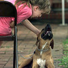 Mika Atkins, 8, gives her Boxer, Sambo, a pet on the head as they prepare for the Overton Kid's Pet Show at McMillan Library Thursday. Matula photo.