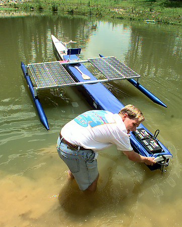 """Reggie Shaw checks the batteries on the """"Half Cat"""" solar-powered boat designed by a team of students at LeTourneau Univ. He and Mike Humy were taking it out on the school's pond for a test drive Thursday. Matula photo."""