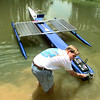 "Reggie Shaw checks the batteries on the ""Half Cat"" solar-powered boat designed by a team of students at LeTourneau Univ. He and Mike Humy were taking it out on the school's pond for a test drive Thursday. Matula photo."