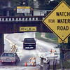 Motorists splash their way through water standing under the Green Street railroad bridge at the intersection with Nelson Street Monday. Matula photo.