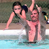 Jody Staples-4, holds her nose as she gets a boost from her uncle Steven Crawford of Hallsville, while they enjoy the Ingram Park pool Monday afternoon in Longview. Kevin Green