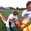 """Lea Barrett, left, ties up the balloon envelope, as her husband and the pilot of the balloon """"Halcyon,"""" the name of a mythical bird that can calm the winds and the waves,  Dennis Barrett of Bogue Chitto, MS.,  looks on as other pilots deflate their balloons Friday morning along FM 1845 in Longview. Kevin Green"""