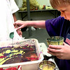 Dennis Davis, 6, mixes paint in order to create a design for his t-shirt that the Longview Art Museum were marbling t-shirts for the summer art camp for kids Wednesday afternoon at the museum in Longview. Kevin Green