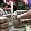 Manuel Flores-8, left, and Jeffery Collins-8, watch as Brian Miller, a potter at Marshall Pottery, smoothes a large mug on the potter's wheel, during a field trip for the G. K. Foster summer school retention program, Thursday morning in Marshall. Kevin Green