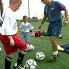 Jeremy Woosham-8, left, from New York St. gets some one on one ball drills by LeTourneau soccer coach Steve Barrett, right , Monday morning during the soccer camp at LeTourneau University in Longview. Kevin Green