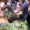 Darnel Ward, left, David Coleman and Walter Ward load up turnip greens and green tomatoes for customers and the Turnip Green Festival in Easton Saturday. They are with D&W Farming. Matula photo.