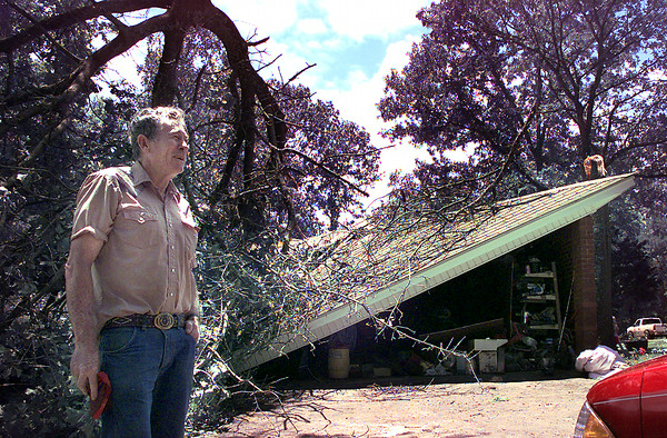 Gene Wacasey. looks to see if there is any damage on his wife's car, after a tree was twisted off and dropped onto his garage and collapsed it, early Tuesday morning off of north White Oak Rd. on Seagull. Kevin Green