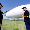 Gregg County Airport Police officer Don Williams visits with Mike Norfolk, ground crewman for Airship Operations out of Orlando, FL. The advertising blimp was forced into the airport because of high winds while travelling from California to New Jersey. Matula photo.