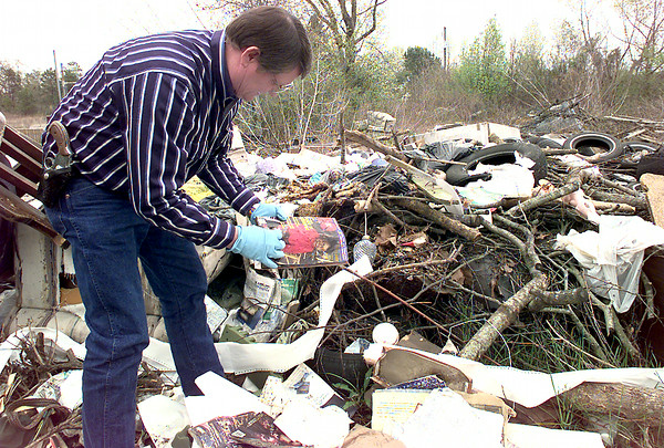 Kenneth Freeman the litter control officer for Gregg County goes through some trash that someone has dumped off of Eastman road in Longview. This trash pile there is a magazine with the name of the subscriber on it that might aid in the investigation of the dumpers. Kevin Green