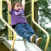 Hope Smith the 3 year old daughter of Brandon and Kim Smith of Longview hangs on tight as she goes airborn on the slide  at Tuegue park in Longview Tuesday afternoon. Kevin Green
