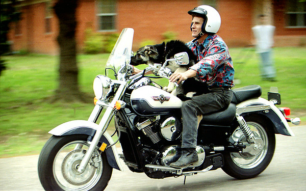 Bobby McCuller gives Silver his 3 month old German Shephard a ride on his motorcycle Monday afternoon off Senic in Longview. Kevin Green