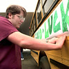 Jonathan Anderson an eleventh grader at Longview High School tapes the good luck banner onto the bus  as the students got a send-off peprally prior to going to UIL competition at the High School in Longview Tuesday morning. Kevin Green