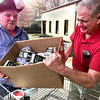 Joe Worsham with Service Paint Co. at the Texas Eastman Plant helps Andy Druschke a volunteer for Longview Community Ministries load a box of hams into a buggy Wednesday afternoon that were donated by Service Paint for the easter project. Kevin Green