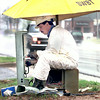 Barry Barnes a splicing technician with Southwestern Bell Telephone stays dry while getting telephone service ready for a nearby shopping center Wednesday afternoon on Judson road in Longview. Kevin Green