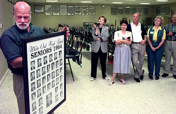 Sonny Blue, left, a 1964 graduate of White Oak High School prepares to hang thier class of 1964 photo of each senior, in the cafeteria at White Oak High School Saturday morning, as other class members gather to watch. Thier class photo had not been hung in the cafeteria for 34 years now. Kevin Green
