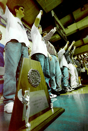 Left to right Justin Smith, left, Adam Wright, middle, and Jeff Slade all raise thier hands for the Pine Tree High School fight song during the closing ceremonies for the University Interscholastic League 4A competition trophy Wednesday morning at the Pine Tree High School gymnasium. Kevin Green