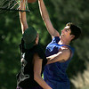 James Harris, 16 left, is not above a little foul play to keep his opponent, Nolen Howard, 18, from making the dunk in a little friendly game of street ball on Dowell St. Tuesday. Matula photo.