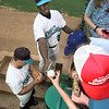 Tyler Wildcatters' #7, left, and #23, reaching for ball, sign autographs for young fans on opening day at Mike Carter Field in Tyler Thursday. Matula photo.