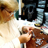 Rebekah Wills, a jewelry maker, restrings some beads from China to make the necklace longer for a customer that brought that brought the original jewelry from the Great Wall. Kevin Green