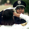LPD officer Judy Ivory shows police Explorer Post #201 member Jennifer Mathis the proper way to salute while looking to fellow officer Gene Duffie (NP) to see if she has the right form Thursday evening before the start of the force's annual memorial service at the Longview Library. Matula photo.