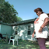 04/07/98--Edith O'Neal stands in front of the siding job a fly-by-night operation screwed up on her house recently. Matula photo.