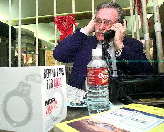 4/1/98---Phil Campbell, covers his ear to hear better as he trys to get donations while being locked up for MDA Wednesday morning at the Longview Mall. Kevin green