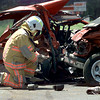 04/23/98--Kilgore FD Rescue Team chief Edgar Rachal takes a moment  and inspects the wreckage of a double fatality accident on Hwy 31, west of Kigore Thursday afternoon. A Ford Escort, to the left, was broadsided by a SUV, right, coming in the opposite direction, killing both passengers of the Escort. Matula photo.