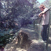 8/25/98---Tammy Simmons stands at the back of her fence where the creek behind her house has eroded nearly up her driveway. After trying retention walls and other methods to stop the erosion, Simmons and her husband put up the fence to protect their young children from a nearly 20 foot fall.
