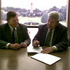 """Date:   7/23/97---Dr. William """"Bill"""" Holda, president of Kilgore Junior College, left, and Dr. Alvin O. """"Bud"""" Austin, president of LeTourneau University, sign an Articulation agreement between the two colleges Thrusday morning at LeTourneau University. The agreement will make it easier for Kilgore student to transfer to LeTourneau.  Jessica Williamson"""