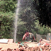Date:   8/19/98----Armando Chavez cools off in a sray of water while working at the demolition site at South Ward Elementary on South Mobberly in Longview. Kevin green