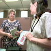 Date:   8/17/98---Barbara Burke, left, electronic services for the city of Longview Library accepts Hepatitis C  books form Sharon Phillips, right, Monday afternoon at the Library. Kevin green
