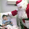 Date:   12/24/98----Dylan Sells the six year old son of Mark and Angela Ethridge, left, looks at a toy as Santa Claus AKA Brian Guthmann, right, delivers gifts to the pedeatric part of GSMC Thursday afternoon in Longview. Brian said he does it because people still need to believe in Santa its a state of mind not a person. Kevin green
