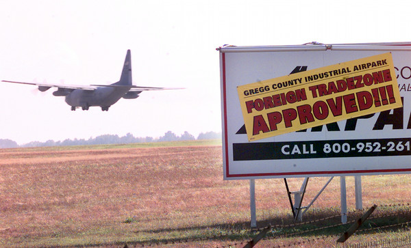 Date:   12/2/98---A plane makes touch and goes Wednesday afternoon at the Gregg County Airport as a sign reflects the new foreign tradeapproved land at the airport. Kevin green