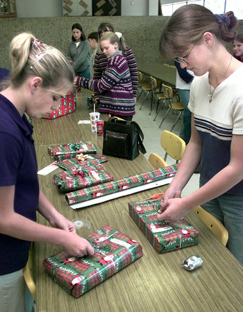 Date:   12/16/98----Judson Middle School eight graders Sarah Parks, left, and Katie Wilson, right, put finishing touches as they wrap gifts they purchased for the Salvation Army Angel Tree Wednesday afternoon at Judson Middle School in Gregg County. Kevin green