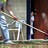Janeshyia Hawkins, 4, looks out her front door to see PT Junior Honor Society president Luke Crowson, 14, raking dirt in the front yard of her mother's new Habitat for Humanity house on E. College Saturday. Members of the society helped sod the Hawkins home as a community service. Matula photo.