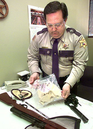 Lt. James Maxwell, with the Gregg County Sheriff's Dept. holds a bag with crack cocaine as guns lay on the desk after they were confiscated during a Tuesday night traffic stop on I-20 at Eastman in Gregg County. Kevin green