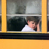 A very bored youngster waits for classmates at Kilgore Intermediate School to board his bus during a very wet and dreary Tuesday afternoon. Matula photo.