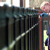 Kendall Wade, with Rosewood Park Cementery on Fm 1844, applies a fresh coat of paint on the fence by the road, Wednesday afternoon outside of Longview. Kevin green