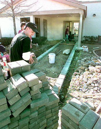 Jeff Hoover, with Aspen Square Management, carries bricks in preparing to lay a brick sidewalk for the new fitness center at Princeton Apartment Complex on Hawkins in Longview. Kevin green