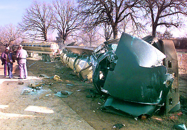 DPS Troopers visit at the crash site of an 18-wheeler tanker that overturned on N. Fuller Rd. just north of FM 1844 early Wedneday morning outside of Longview. Kevin green