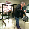 Curtis Watson, with the maintenance dept. at Spring Hill ISD, sweeps up glass in the foyer of the gym Thursday morning after wind had damaged the high school in LOngview. Kevin green