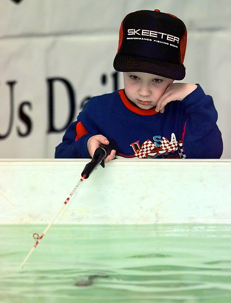 Patrick Mahaffey, 5, gets a little tired of waiting on the rainbow trout at the Texas Parks & Wildlife Dept. fishing hole during the Longview Partnership Boat Show at Maude Cobb and  the fairgrounds exhibition hall Friday. Matula photo.