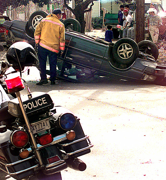 A Longview Firefighter looks at the damage to a car while it lays upside down in the 1100 blk. of 12th St. after John Adams hit a car from the rear they overturned Friday afternoon in LOngview. kevin Green