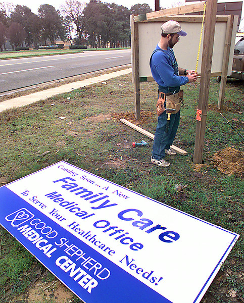 William Boney, with Sign Pro of Longview, measures for a sign announcing Good Shepherd's newest facility on Mobberly across from LeTourneau University, Wednesday morning in Longview. Kevin green