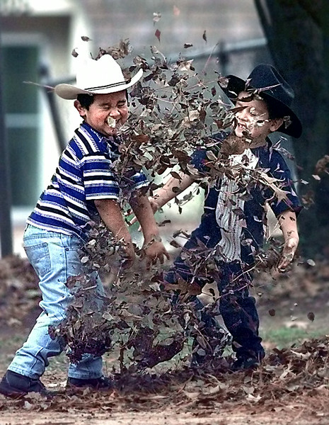 Jose Ramon, 4 left, gets a face full of Autumn from brother John Barrios, 4, as they play in their backyard on Short St. in Longview Saturday. Matula photo.