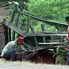 Date:   7/21/98---A volunteer fireman stands near as a wrecker company employee using a cutting torch works on a flatbed trailer after the rig pulling it was hit by a train Tuesday afternoon in Pritchett. Kevin green