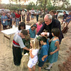 Date:   7/15/98---The Rev Carmody gets a little help from the kids during a groundbreaking ceremony fo rhte new catholic church Wednesday evening in Hallsville. Kevin green