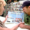 Date:   7/28/98---R. K. Coley, left, owner of Video Zone looks over an Entertainment Preview magazine with Larry Kirby, right, of Arp, as she shows him the two page Titanic layout Tuesday afternoon at the Video Zone on McCann Rd. in Longview. Kevin green