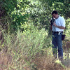Date:   7/10/98---LPD Det. Kirk Haddix video tapes the body found in a wooded area on Ray St. Friday afternoon in Longview. Kevin green